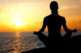 Meisje mediteert bij zonsondergang
